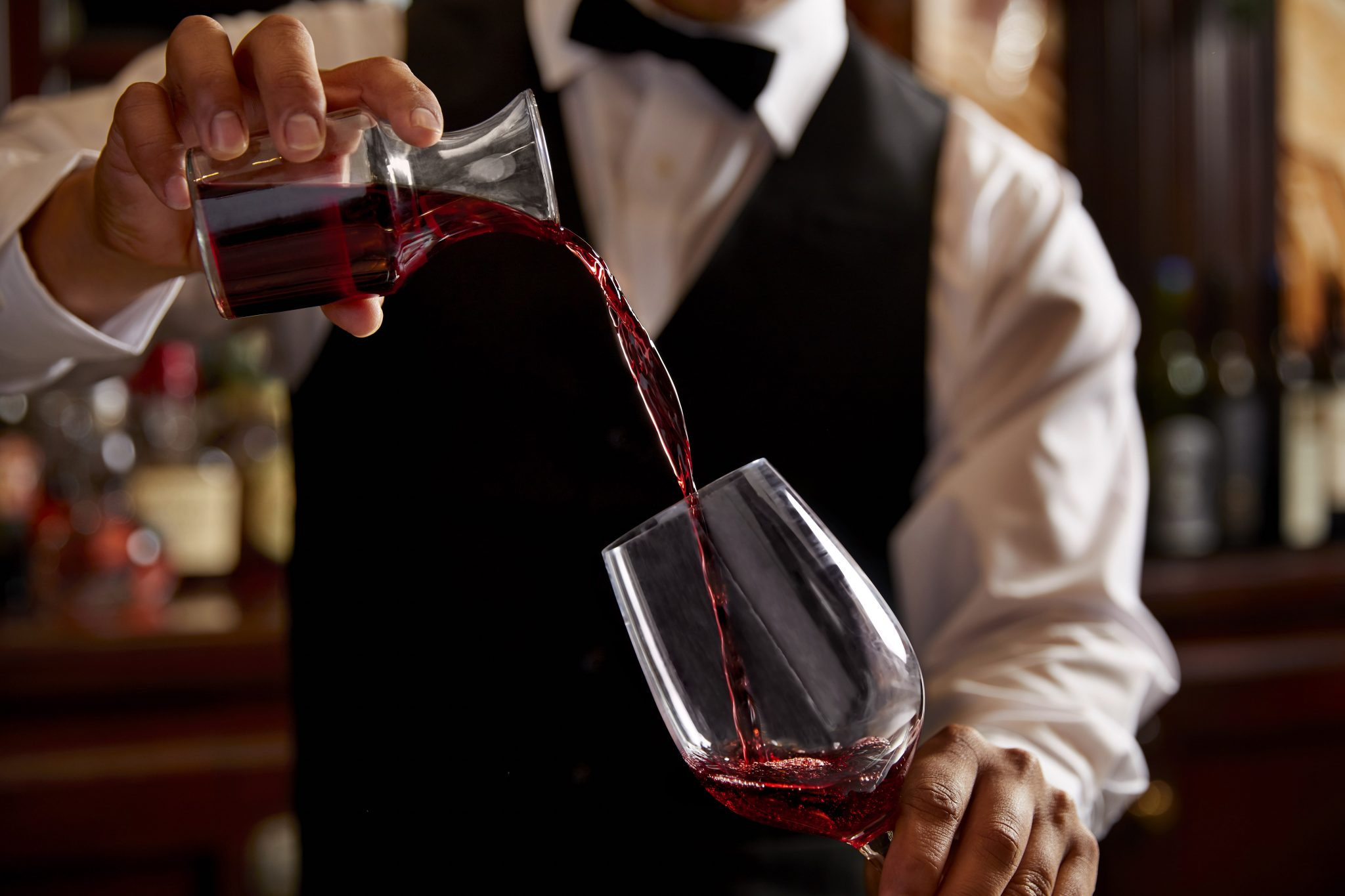 A bartender wearing a vest and bowtie pouring red wine from a carafe into a glass