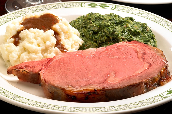 a plate of rare prime rib with mashed potatoes, gravy, and creamed spinnach